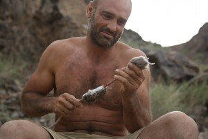 Ed Stafford crouched down next to his home with a stick and mouse in hand in the hills in Mongolia.
