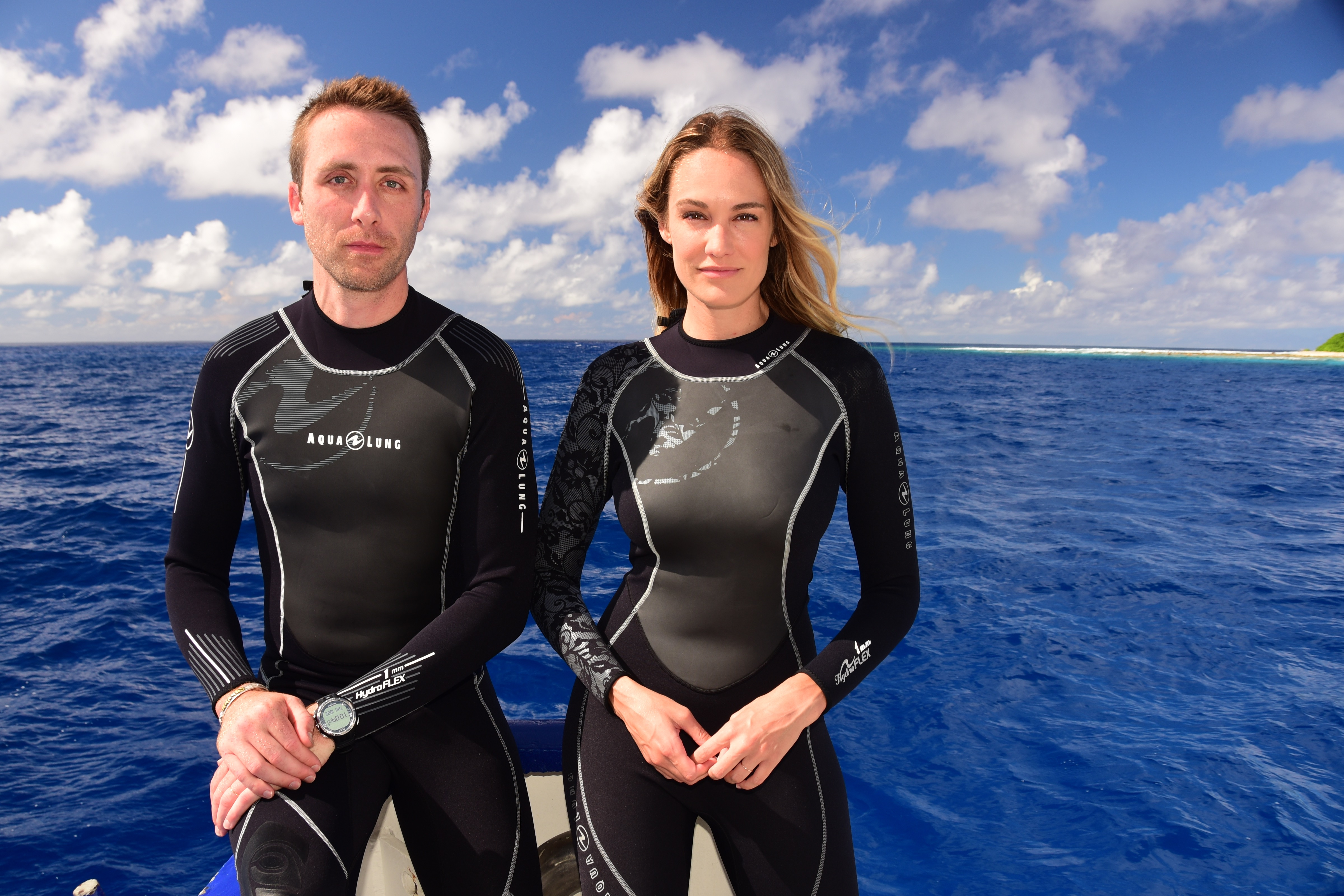 Philippe and Ashlan Costeau in wet suits on a boat.
